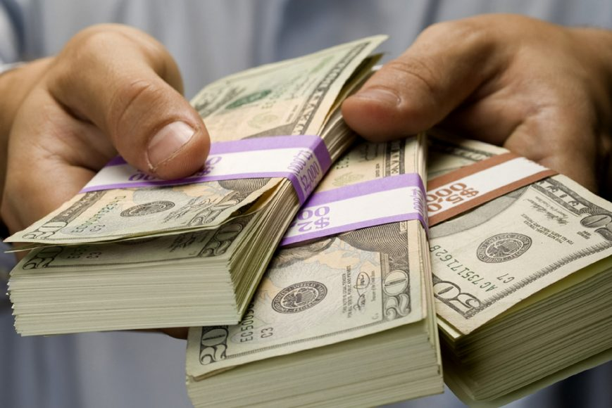 Hands holding several big stacks of money