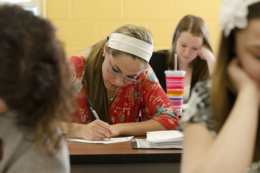 Focus on a student writing in a classroom setting wearing a large white headband