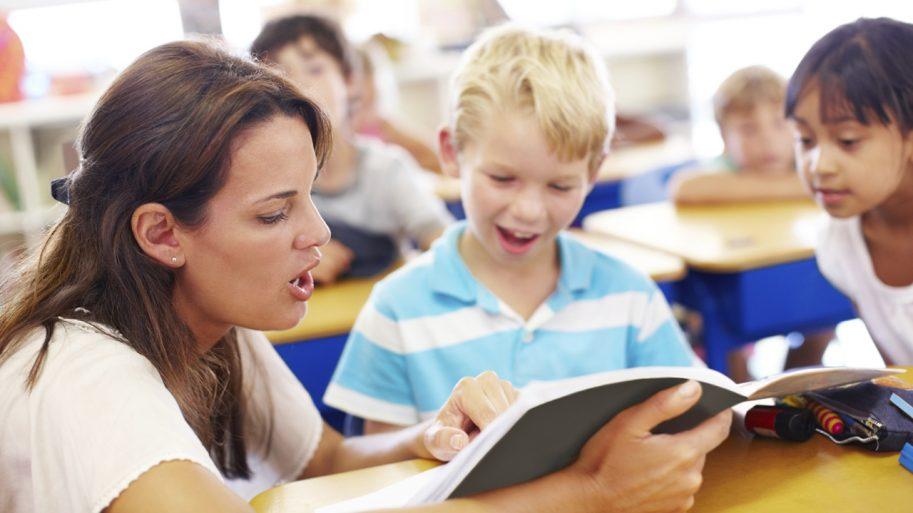 Teacher reading a book to a child