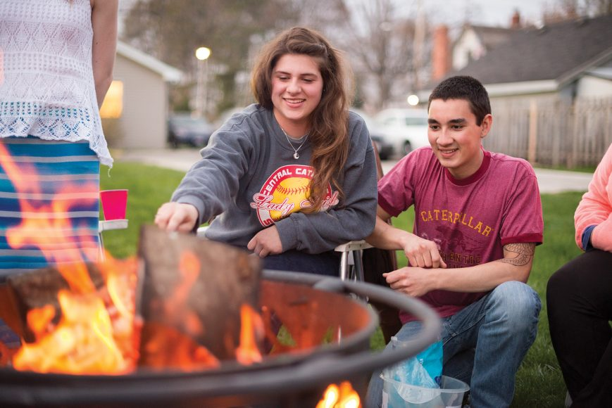 Students smiling in front of a fire pit