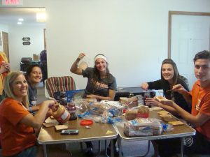 group photo of students sitting at a table with snack food