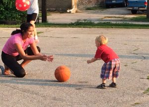 a young child rolling a basketball towards a student helper