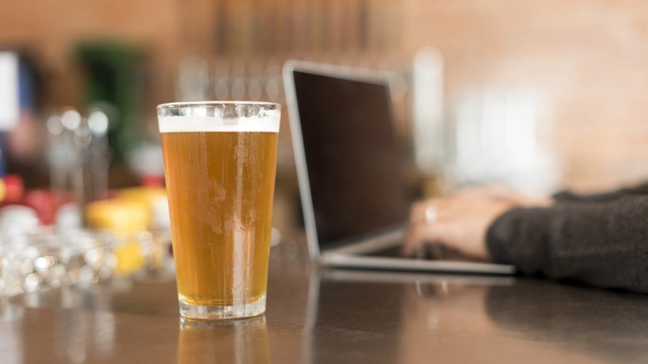 Glass of beer next to a laptop