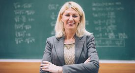 Portrait of mature academic person, female professor standing near blackboard with math formulas. Woman is 50-60 years old, with blonde hair and sophisticated appearance.