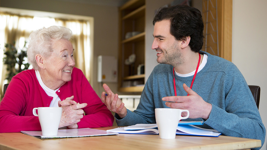 Friendly Male Volunteer Assisting a Senior Woman With Paperwork