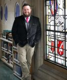 Admissions staff member wearing a suit with a stack of books behind him and stained glass window