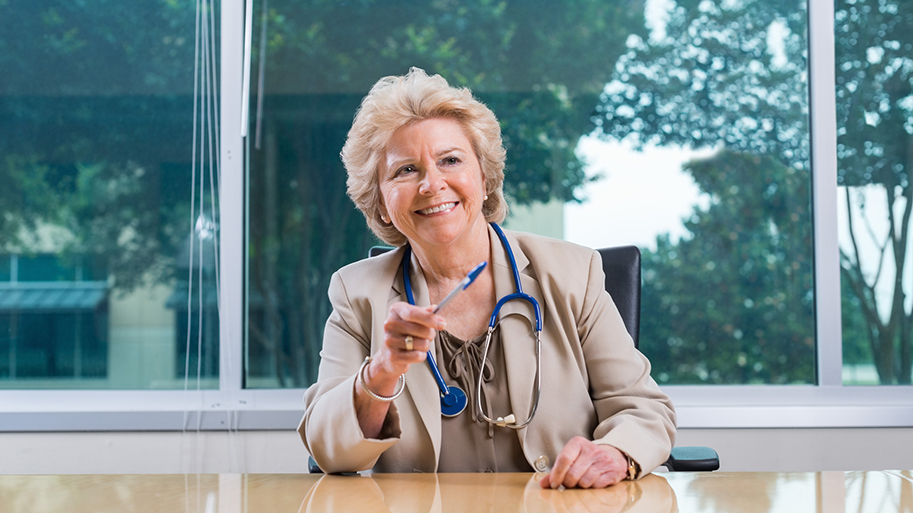 Senior adult Caucasian female doctor is seated at head of board room table during hospital staff meeting or board meeting. She is wearing a suit and stethescope, while talking to coworkers off camera. Woman has short blonde hair and a toothy smile. There are large windows behind her in modern board room with a window behind her.