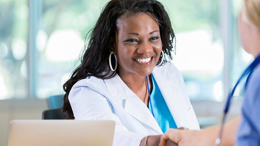 Cheerful African American female doctor warmly greets a female associate.