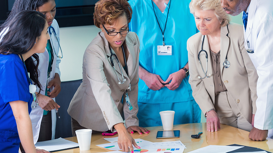 Diverse mid adult nurses, mature adult hospital adminstrators, and senior adult doctors are standing around table in hospital board room. They are reviewing spreadsheets and charts containing financial information for hospital during board meeting. Staff is wearing professional clothing, scrubs, and lab coats.