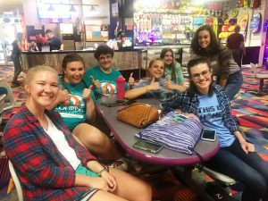 Students smiling around table at bowling alley