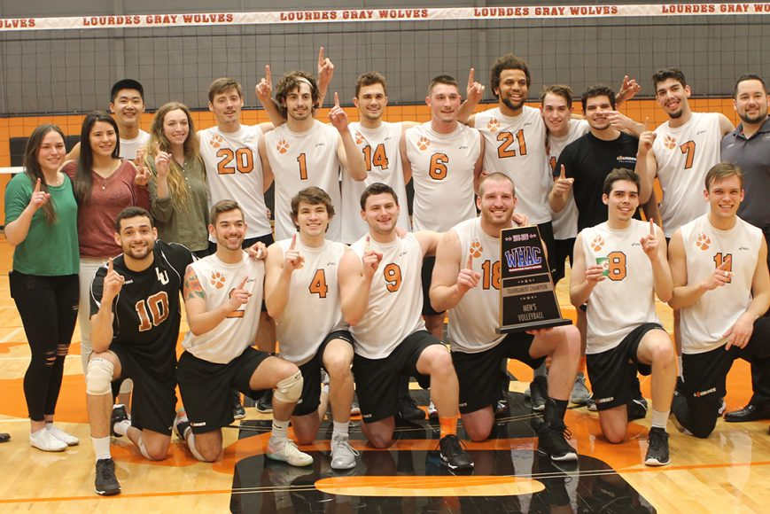 Lourdes University mens volleyball team posing for photo with each team member holding up #1 sign on the volleyball court