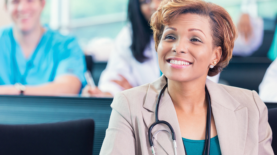 Mid adult African American professional hopsital adminstrator or doctor is smiling while sitting in lecture hall style meeting room. She's attending a healthcare conference or medical seminar at hospital with diverse doctor and nursing staff.