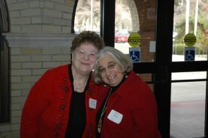 Two older ladies wearing red sweaters standing in front of the door