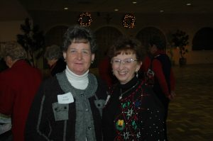 Two older ladies wearing sweaters who are standing in a room with Christmas wreaths in the background