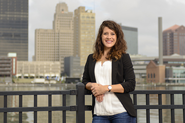 Person standing leaning against a railing with a city in the background