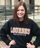 Student wearing a black Lourdes University sweatshirt outside