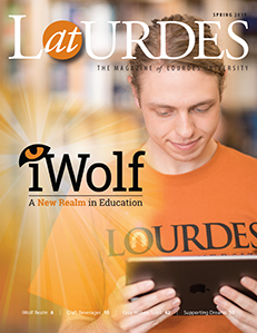 Male student wearing an orange Lourdes University t-shirt holding a tablet with light shining behind him displaying the iWolf logo