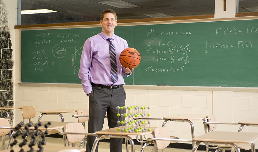 Teacher standing in a classroom holding a basketball with a green chalkboard in the background