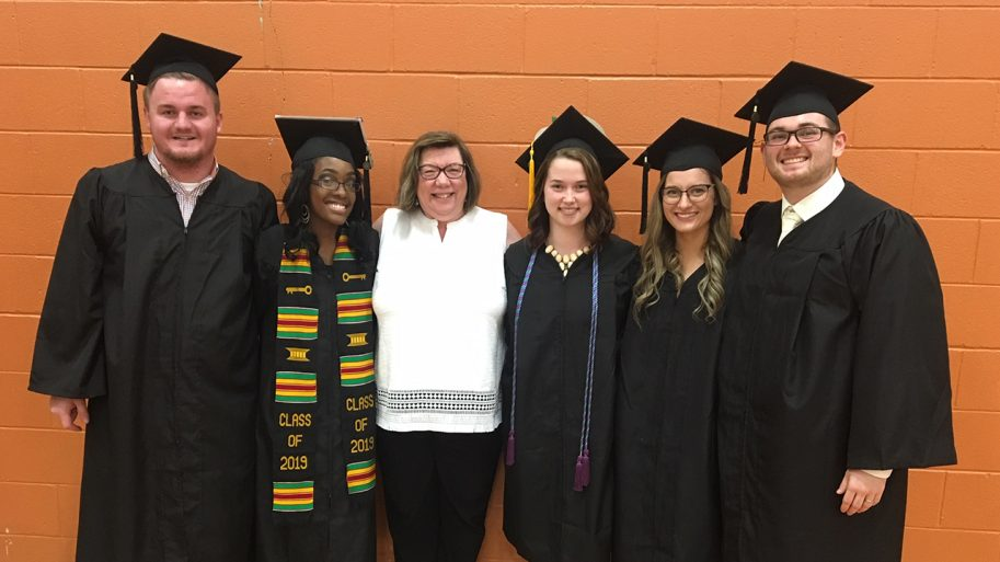 Five high school graduates with black caps and gowns with the Director of the Arches program