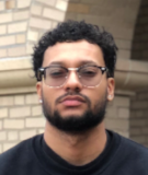 Student with a black t-shirt wearing glasses