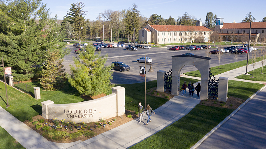 Campus with students walking and parked cars showing the Lourdes University main entrance