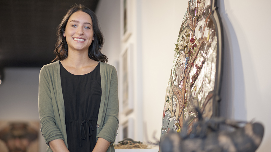 Art student standing next to artwork with branches and flowers