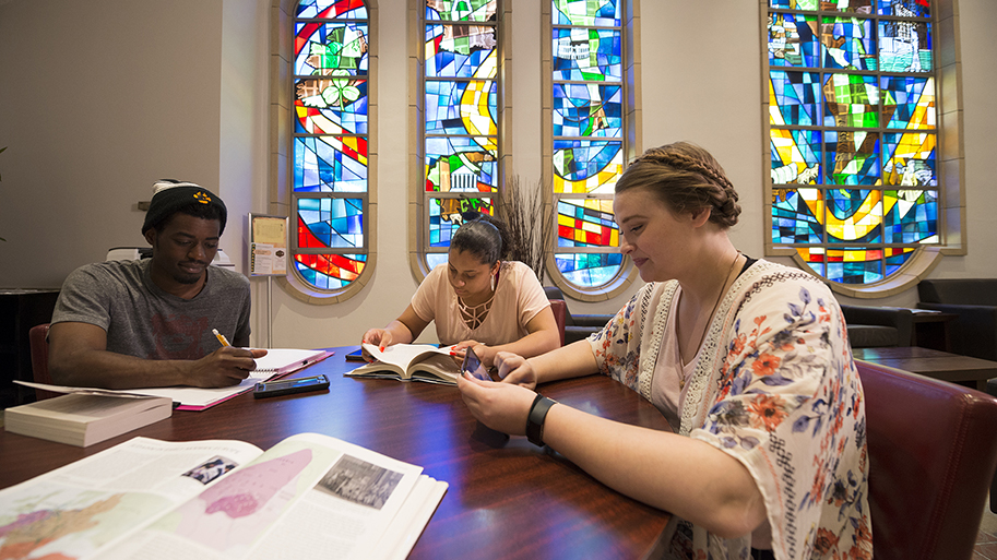 Three students studying at a table reading books, taking notes, and using a tablet