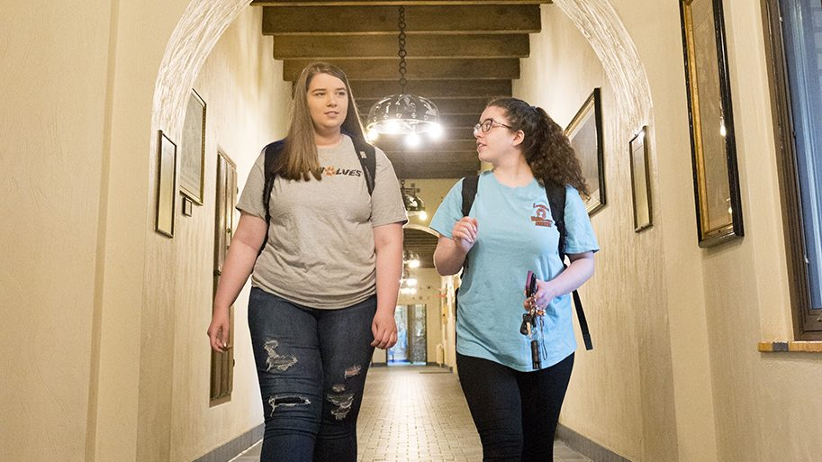 Students walking in a hallway inside campus