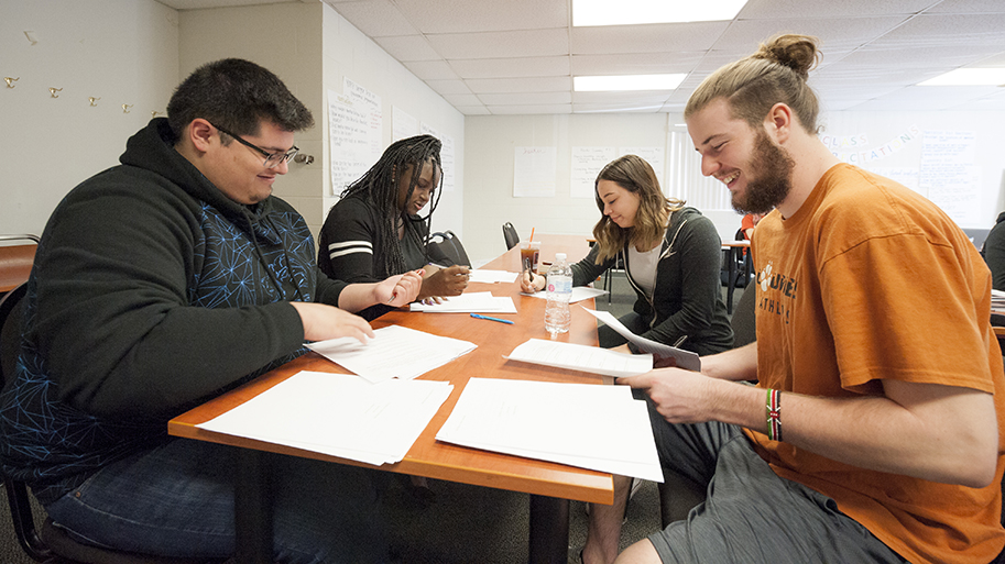 Students sitting at a table reading papers