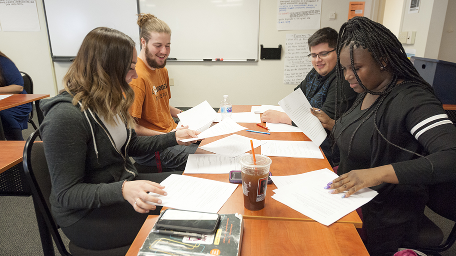 Four students sitting around a table reading papers