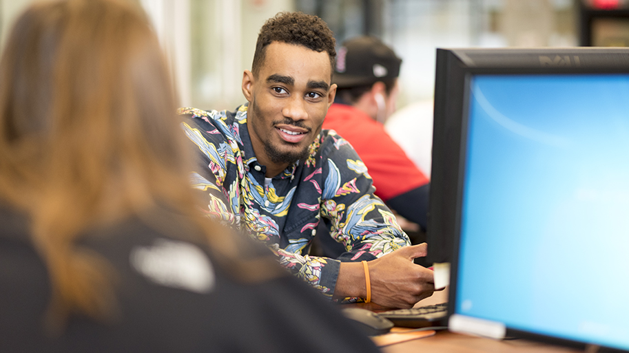 Student next to a computer monitor