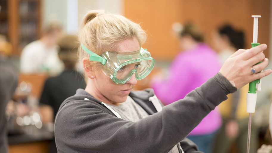 Close of up a female student wearing protective goggles using equipment