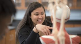 Student in front of aquatic vibrant artwork