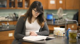 Student reading a textbook in a lab