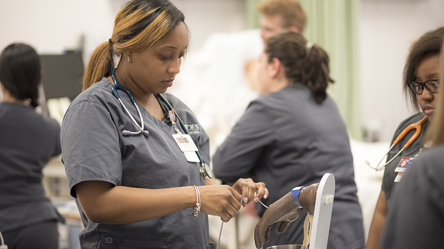 Nursing student using a simulated hand to practice