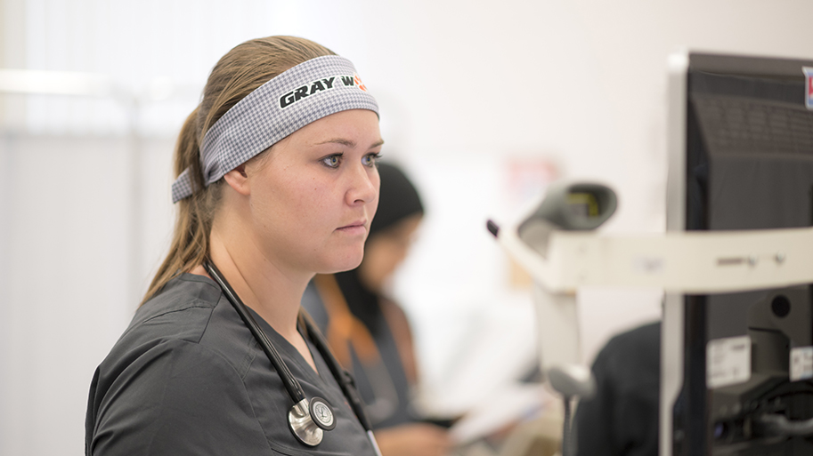 Female nursing student looking at a computer monitor