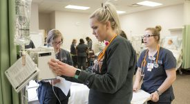 Several nursing students reviewing reports and using equipment