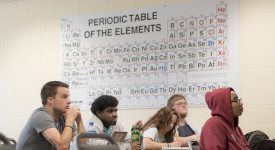 Students in a classroom at desks with the periodic table of elements on the wall