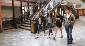 Four students walking indoors on campus