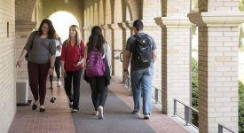 Students walking outside on campus under arches
