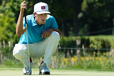 Golfer looking closely at a hole while holding his club