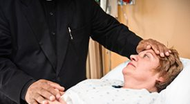 Photo of a pastoral professional comforting someone at their bedside