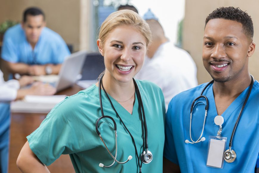 Two RNs in workplace in front of nurses station