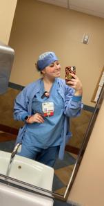 Photo of Noelle Miller taking a selfie on break and dressed in scrubs
