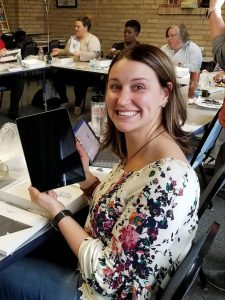 Photo of Sarah Thomas smiling and holding an iPad during iWolf training for the Lourdes Nursing department
