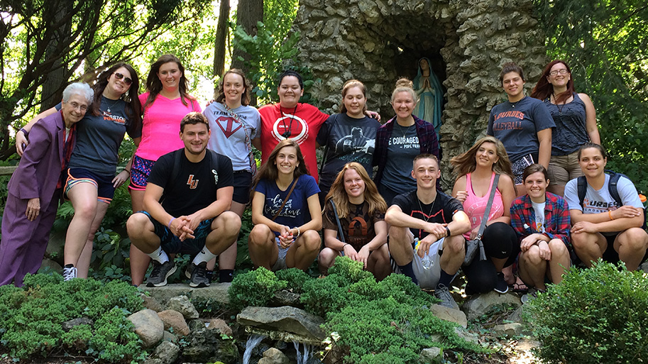 Tau Scholars In Front Of The Grotto On Campus Grounds