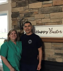 Photo of Tracy Rodriguez and her husband Trinidad near fireplace with Happy Easter sign