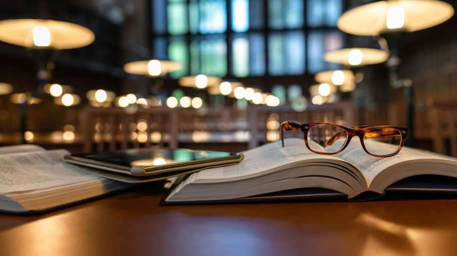 Photo of mobile device, books and glasses inside a library