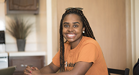 Lourdes Female Student Smiling While In Apartment Style Campus Housing