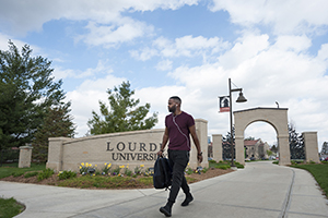 Photo of Student walking on campus near entryway